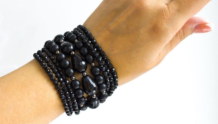 Черный браслет на руке из минералов